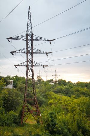 A landscape with several powerful power lines against the green forest and sunset sky, soft focus