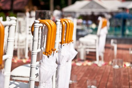 Closeup of a row of white chairs, white umbrellas are hanging on the backs of chairs in case of rain, selective focus
