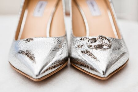 Closeup of the brides silver shoes toes and wedding rings on the marble floor, selective focus 版權商用圖片