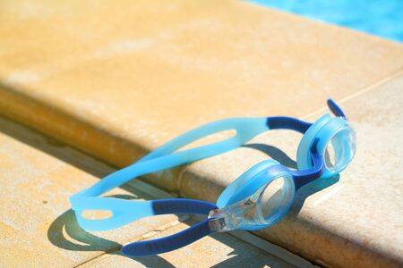 A light blue goggles for swimming lie on the side of the swimming pool on the background of crystal clear water Stock Photo
