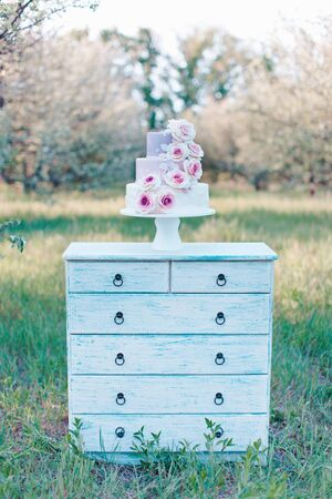 A three tiered wedding cake in pastel colors, decorated with realistic pink roses, stands on a white camo against a blurred background of a garden, selective focus