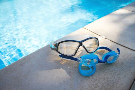 Two blue goggles for swimming lie on the side of the swimming pool against the background of crystal clear water