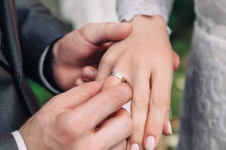 Nahaufnahme der Hand des Bräutigams legt einen Ehering auf den Finger der Braut, die Zeremonie auf der Straße, selektiver Fokus