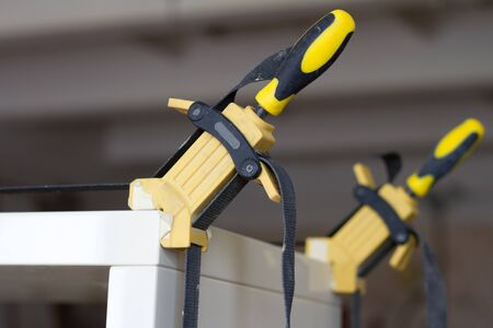 Gluing and fixing wooden furniture with a few clamps on a blurred background of carpentry workshop, selective focus