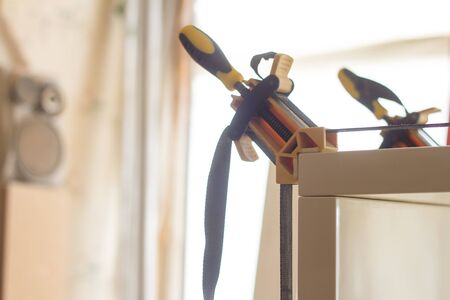 Gluing and fixing wooden furniture with a few clamps on a blurred background of carpentry workshop, selective focus Banco de Imagens - 128365076