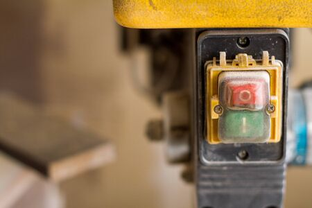 Closeup circular saw switch with two green and red buttons, selective focus Imagens - 128340647