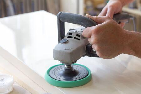 Un carpintero pule la superficie de la fachada antes de montar los muebles en un taller de carpintería de fondo borroso, enfoque selectivo