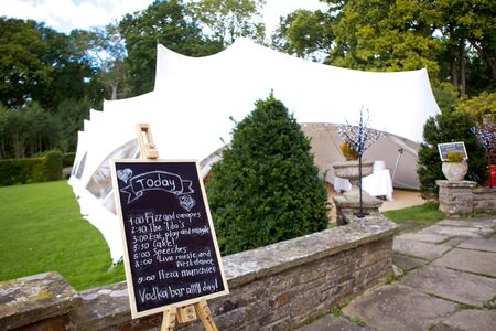 A wedding Pavilion for guests and a black board with a written schedule of wedding events, selective focus