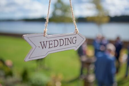 A wooden direction with wedding text is hanging near location of the ceremony, selective focus