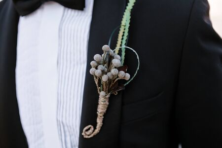 Closeup of boutonniere with the decor on a grooms black elegant jacket, selective focus