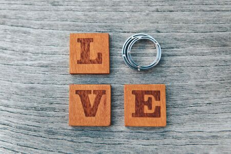 Closeup of the word Love consists of letters and wedding rings on a gray wooden background, selective focus