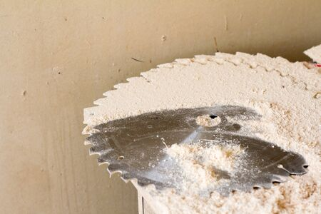 Closeup of a heap of fine carpentry dust near a working circular saw and on disks for a circular saw, selective focus
