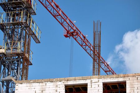 Closeup of a construction crane working against the backdrop of a new building and blue sky, selective focus Imagens
