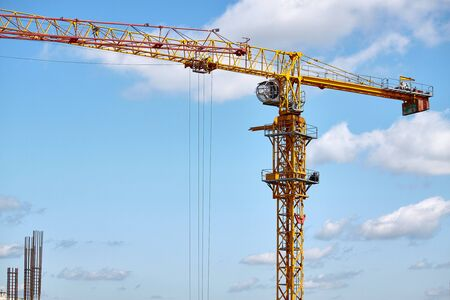 Construction of a highrise building, operation of a tower crane against a blue sky, selective focus
