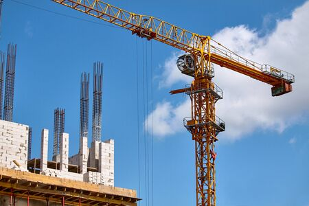 Construction of a highrise building, the formation of cement supports and the operation of a crane against a blue sky, selective focus Banque d'images