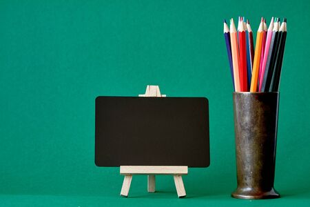 A miniature chalk board on an easel and multicolored pencils in a metal stand isolate on green background, concept back to school, selective focus