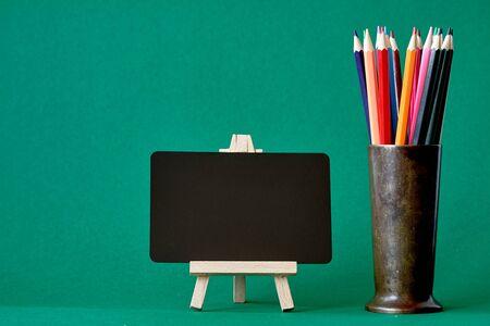 Eine Miniatur-Kreidetafel auf einer Staffelei und mehrfarbige Bleistifte in einem Metallständer isolieren auf grünem Hintergrund, Konzept zurück zur Schule, selektiver Fokus