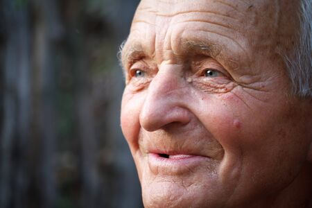 Closeup portrait of a very old man against the background of wattle, selective focus