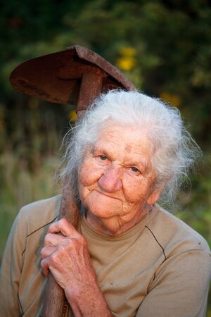 Closeup portrait of an old woman with gray hair smiling and looking at the camera, holding a rusty shovel in her hands, face in deep wrinkles, selective focus