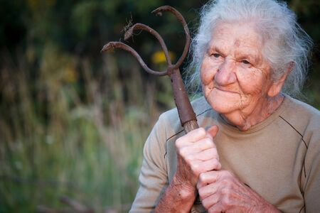 Closeup portrait of an old woman with gray hair holding a rusty pitchfork or chopper in her hands, face in deep wrinkles, selective focus