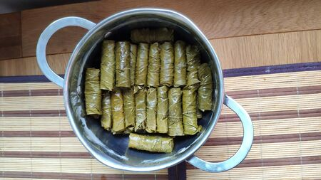 Top view of pan with Dolma, tolma, sarma, dolmah stuffed grape leaves with rice and meat, traditional Caucasian, Ottoman, Turkish and Greek cuisine
