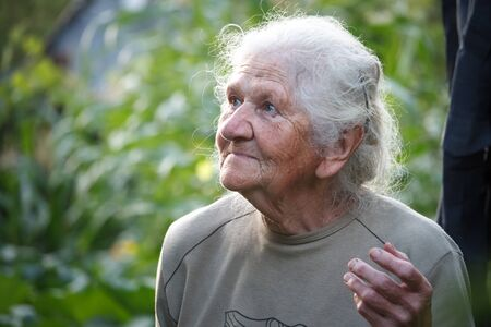 Closeup portrait of an old woman with gray hair smiling and looking up, face in deep wrinkles, selective focus Banco de Imagens