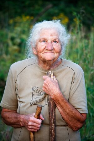 A closeup portrait of an old woman with gray hair smiling and looking up, resting her chin on a stick as if walking with a cane, face in deep wrinkles, selective focus