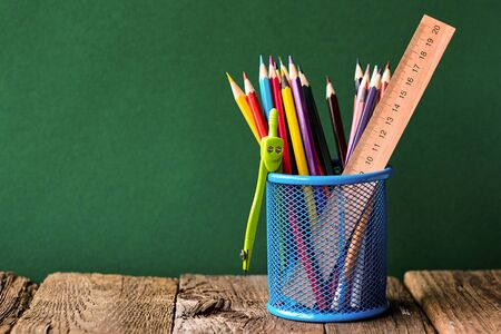 Back to school concept, blue glass with school supplies on an old wooden surface on a background of a clean green chalk board, selective focus, copyspace Stock fotó