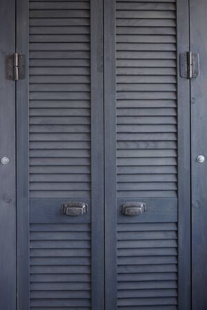 Close up dark gray shutter doors with frayed metal handles, Scandinavian minimalist cabinet interior, selective focus