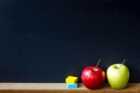 Back to school concept, closeup of a clean black chalk board and two apples red and green, selective focus, copy space