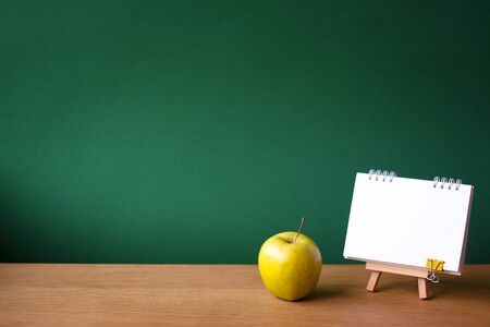 Back to school concept, open notebook on miniature easel and green apple on wooden surface on the backdrop of a clean green chalk board, selective focus, copyspace 免版税图像