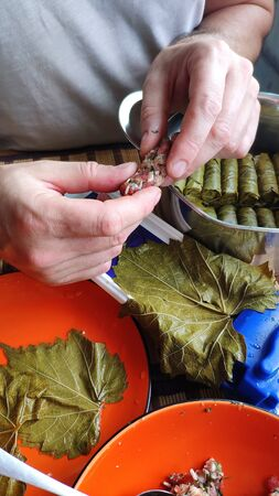 Closeup of male hands making Dolma, tolma, sarma, dolmah stuffed grape leaves with rice and meat using a special device, traditional Caucasian, Ottoman, Turkish and Greek cuisine, selective focus