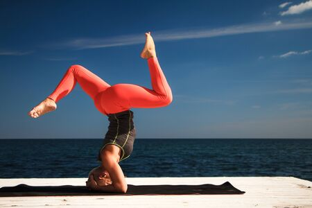 Adult blond woman with short haircut practices yoga on pier against the background of the sea and blue sky Foto de archivo