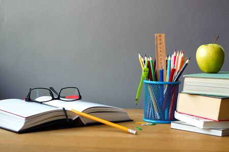 Back to school concept, school supplies, stack of books, green apple and open book with glasses on wooden surface, selective focus