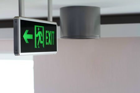 Side view of a green glowing sign with the words Exit and running man, selective focus Stockfoto