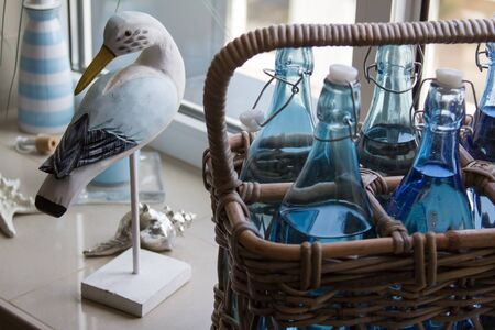 Close up of several glass water bottles in a wicker basket and a decorative wooden bird on the windowsill, selective focus