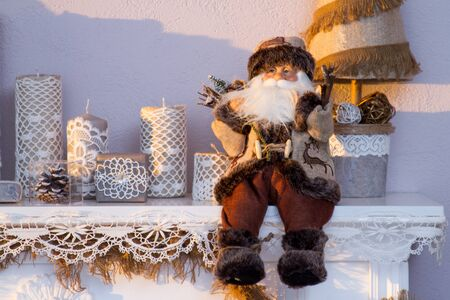 Close up of a toy figure of Santa Claus sitting on a mantelpiece next to several decorative candles, soft focus