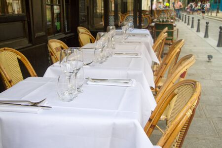 Close up of several served tables with white tablecloths and ward chairs, selective focus