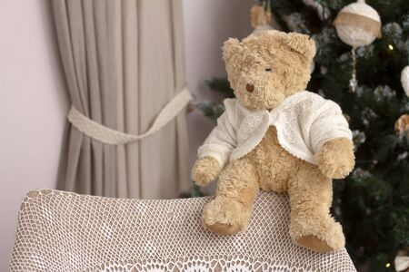 Close up toy Teddy bear on the back of a chair with a handmade knitted wrap on a blurred background of a decorated Christmas tree, selective focus Stockfoto