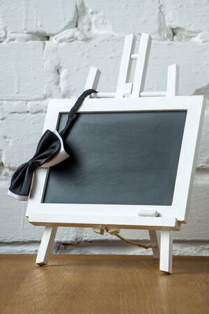 Close up of a miniature chalk board and bow tie on a white brick wall background, selective focus 免版税图像