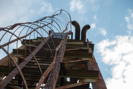 Bottom view of old rusty steps on metal tower, selective focus
