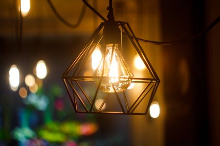 Close up glowing hanging spherical retro vintage edison incandescent bulb in metal lampshade against background of blurred other lamps, selective focus Stockfoto