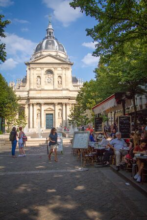Paris, France - July 7, 2018: People sit at tables on the summer terrace of the cafe in front of the main entrance of university Sorbonne in Paris Éditoriale