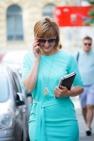 Adult middle-aged business woman with documents in her hands walking down the street and talking on a smartphone, selective focus Stok Fotoğraf - 130383131