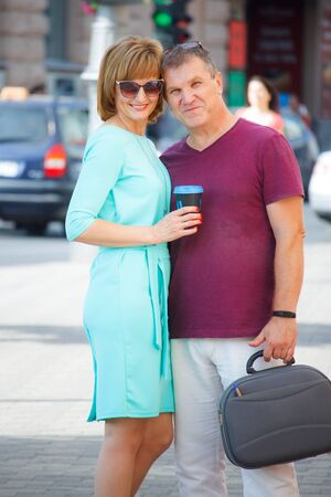 Middle-aged couple smiling and hugging on a city street, selective focus