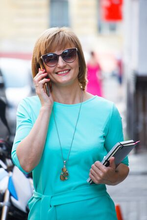 Adult middle-aged business woman with documents in her hands walking down the street and talking on a smartphone, selective focus