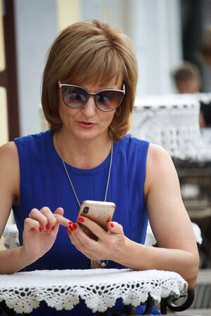 Adult middle-aged business woman sitting on the street at a cafe table and checking email on a smartphone, selective focus Stok Fotoğraf - 130499158