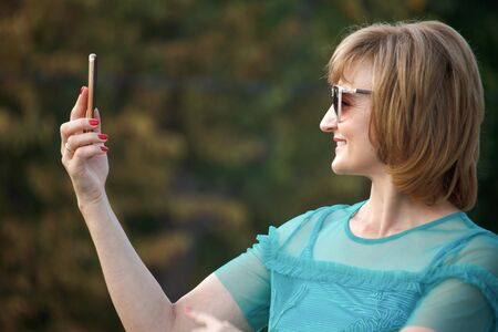 Adult middle-aged business woman on the street makes selfie on a smartphone, selective focus Stok Fotoğraf - 130565107