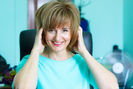 Portrait of a smiling adult middle-aged business woman on the background of the office, selective focus Stok Fotoğraf - 130565115