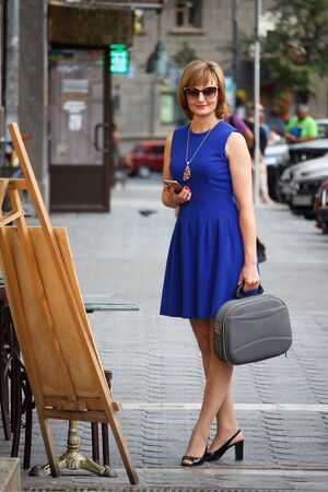 Middle aged adult business woman stands on the street with a smartphone and a case with a laptop and smiles at the camera, selective focus Stok Fotoğraf